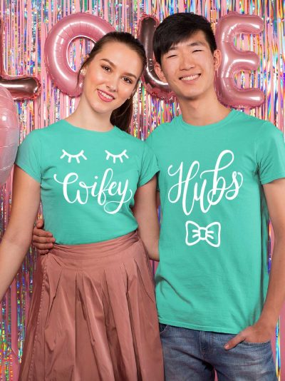 man and woman sitting close smiling wearing Hubs and Wifey Couple T-shirt