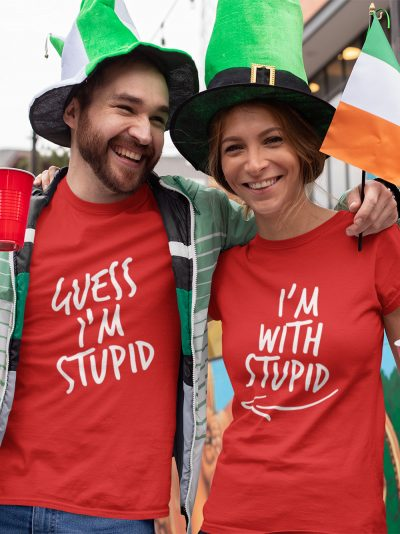 man and woman standing close and smiling wearing I am with stupid Red Couple T-shirt