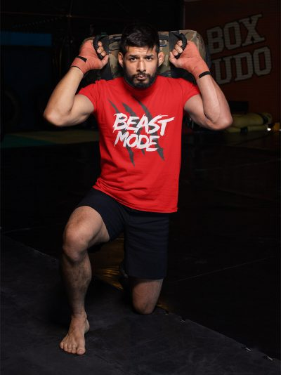 man wearing Beast Mode T-shirt and kneeling to lift weight
